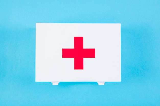 Overhead view of first aid kit with medical sign on blue backdrop