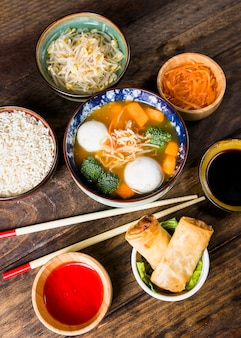 An overhead view of fish ball soup; rice; beans sprouts carrot and spring rolls with sauces and chopsticks over the table