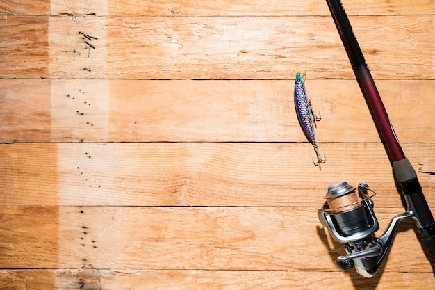 An overhead view of fishing lure with fishing rod on desk