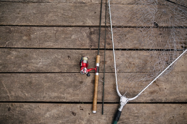 Overhead view of fishing rod and net on wooden pier