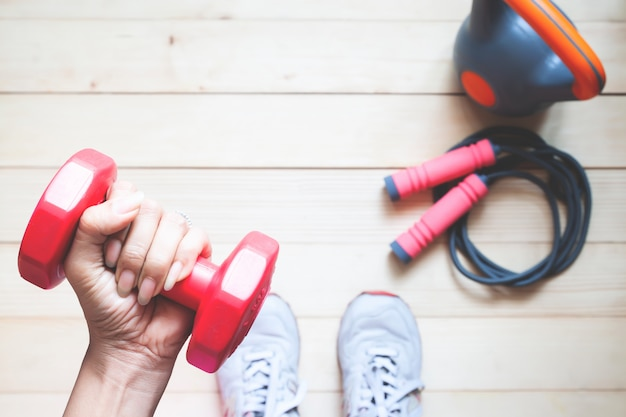 Overhead view of fitness girl holding red dumbbell with fitness equipments on wooden floor.