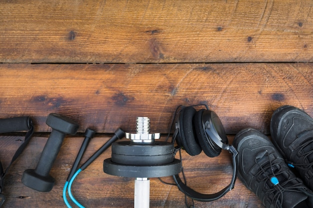 An overhead view of fitness strap; dumbbells; skipping rope; weights; headphone and shoes on wooden textured background
