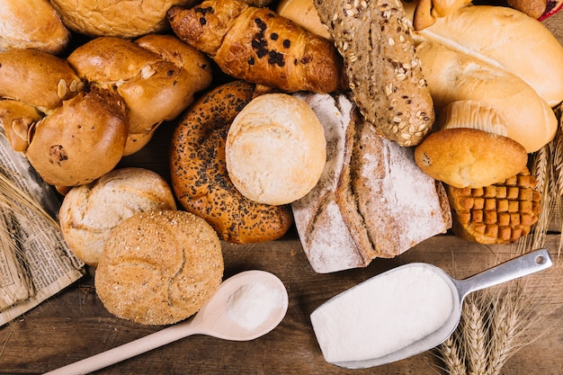 An overhead view of flour with baked whole grain breads on table