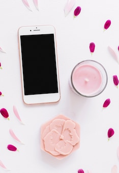 An overhead view of flower shape soap; candle and smartphone decorated with petals