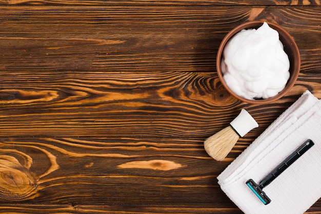 An overhead view of foam bowl; shaving brush; razor and white folded napkin against wooden textured backdrop