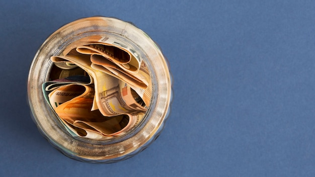 An overhead view of folded euro notes in an open jar on colored background