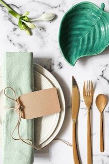 An overhead view of folded napkin tied with tag on ceramic plate and cutlery over marble textured background