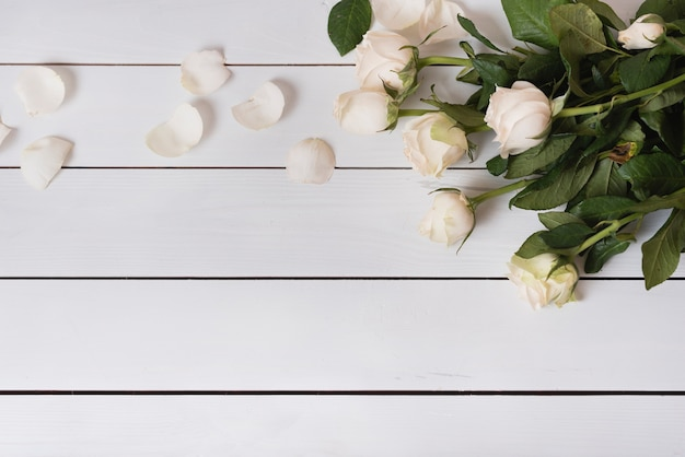 An overhead view of fresh beautiful white roses on wooden table