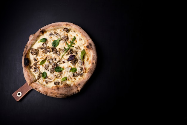 An overhead view of fresh cheesy mushroom pizza on wooden board over black kitchen worktop