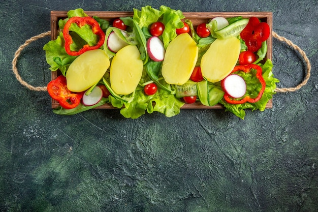 Overhead view of fresh chopped vegetables on a wooden tray on mix colors background with free space