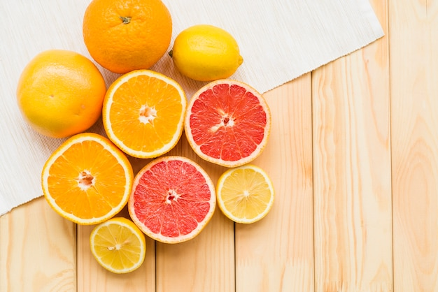 Overhead view of fresh citrus fruits on wooden background