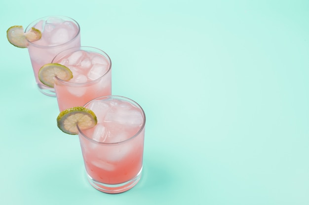 An overhead view of fresh cocktail with lemon slice and ice cubes on mint background
