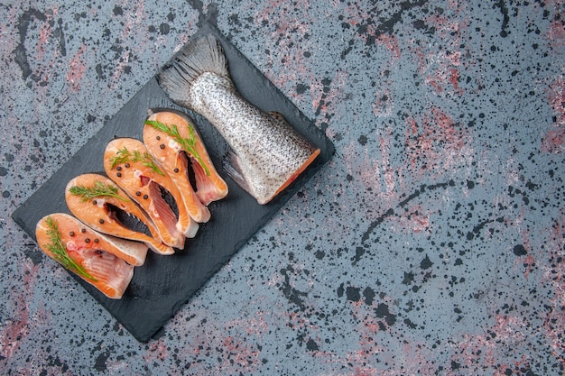 Overhead view of fresh cut raw fishes green on dark color tray on the left side on blue black mix colors table with free space