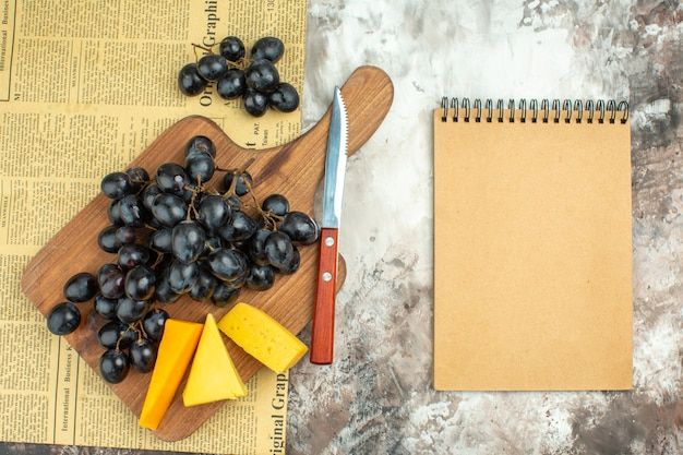 Overhead view of fresh delicious black grape bunch and various kinds of cheese on wooden cutting board