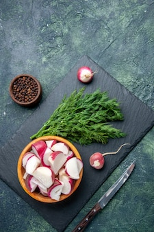 Overhead view of fresh dill bundle and whole chopped radishes knife on black cutting board pepper knife on green black mix colors background with free space