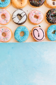 Overhead view of fresh donuts in box on blue backdrop