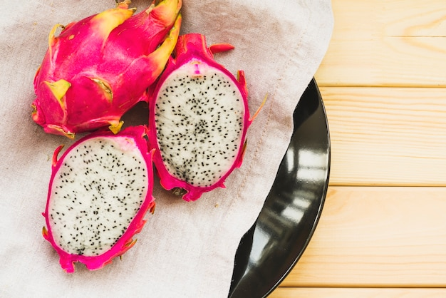 Overhead view of fresh dragon fruits on wooden table