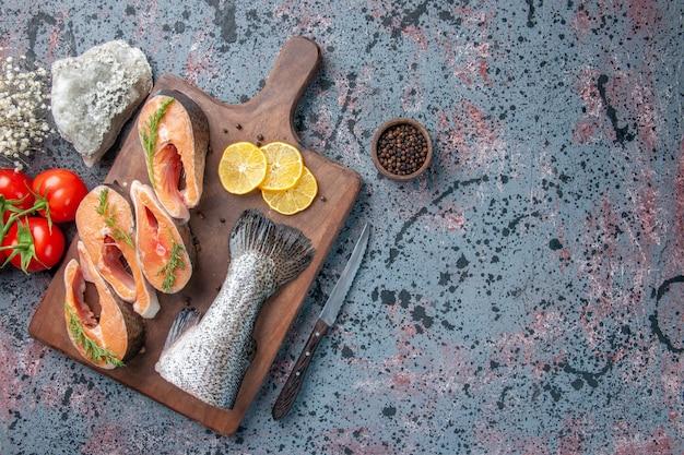 Vista dall'alto di pesci freschi fette di limone verdi pepe sul tagliere di legno e coltello sulla tabella di colori mix nero blu