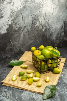 Overhead view of fresh kumquats and lemons in a black basket on newspapers on gray background stock image