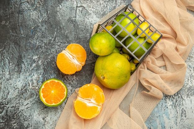 Vista dall'alto di limoni freschi in un cesto nero caduto su un asciugamano su un tavolo grigio fotografia stock