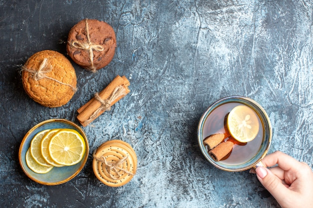 Overhead view of fresh lemons and hand holding a cup of black tea with cinnamon various stacked cookies on dark background