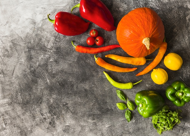 An overhead view of fresh organic vegetables on textured background