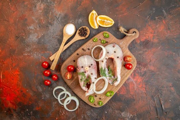 Vista dall'alto di pesce crudo fresco e pomodori verdi cipolla pepe su tagliere di legno su superficie di colore misto