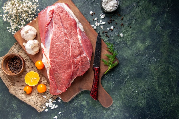 Vista dall'alto di aglio verde di carni rosse crude fresche su tagliere di legno marrone pomodori pepe su coltello asciugamano colore nudo su sfondo di colore scuro