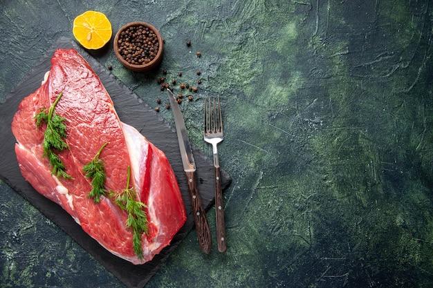 Vista dall'alto di carne cruda rossa fresca verde su tagliere e posate al limone pepe messe sul lato destro su sfondo verde nero mix di colore