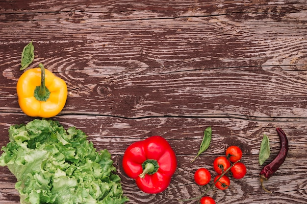 An overhead view of fresh salad ingredients on weathered wooden table