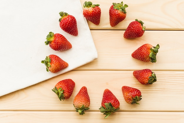 Overhead view of fresh strawberries forming circles on wooden background
