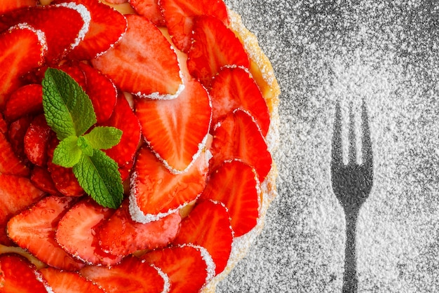 Overhead view of fresh strawberry pie with berries on gray