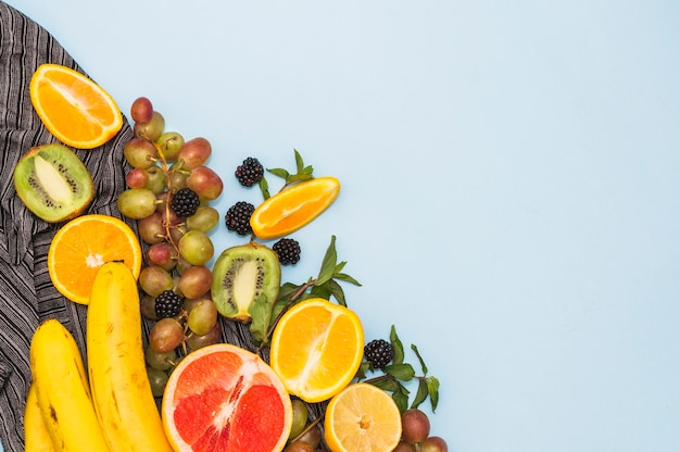 An overhead view of fresh tropical fruits on blue background