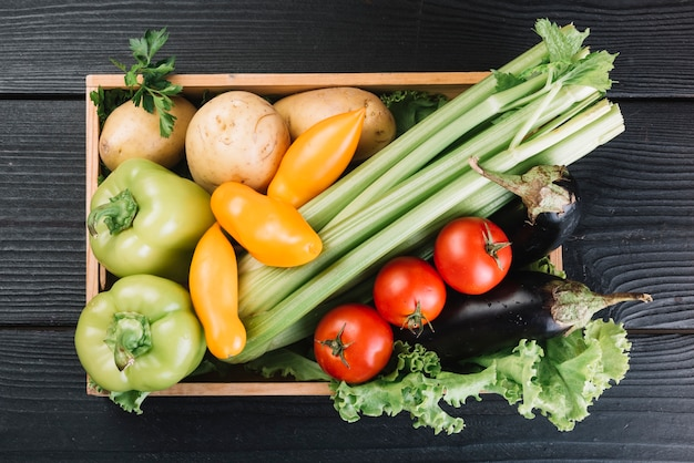 Overhead view of fresh vegetables in container on black wooden background