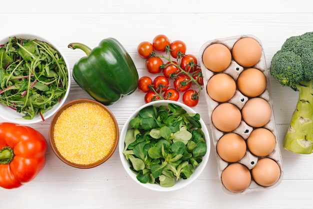 An overhead view of fresh vegetables; eggs and polenta on white wooden desk