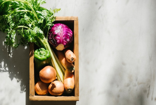 Overhead view of fresh vegetables in wooden tray
