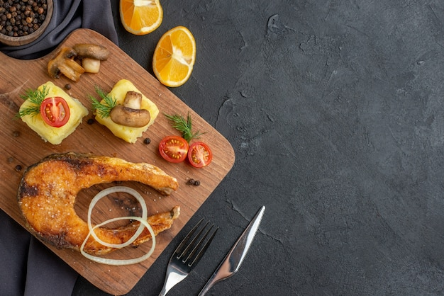 Overhead view of fried fish meal with mushrooms vegetables cheese on wooden board lemon slices pepper on dark color towel cutlery set on black distressed surface