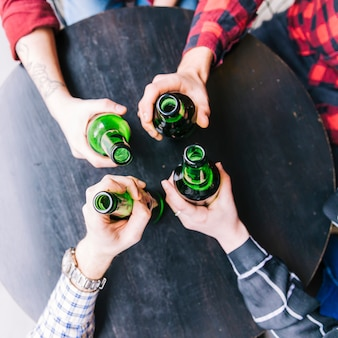An overhead view of friend's hands holding the green beer bottles on black wooden table