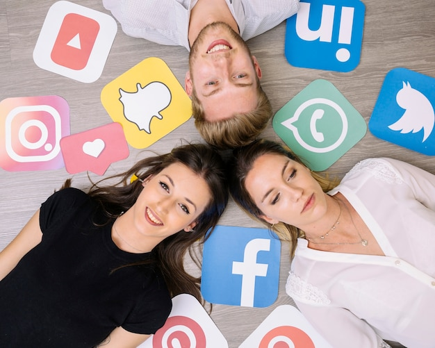 Overhead view of friends lying on backdrop with social media icons