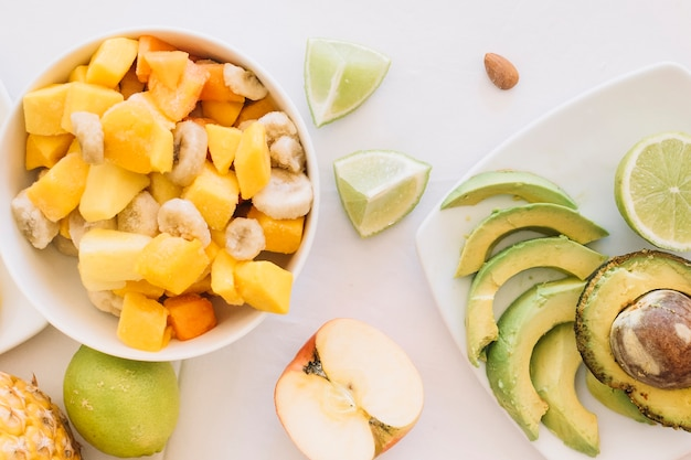 An overhead view of fruit salad bowl and avocado slices on white background