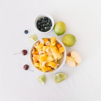An overhead view of fruit salad bowl on white background