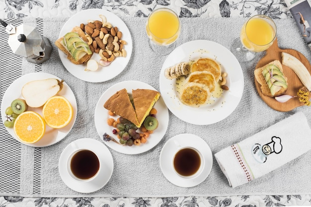 An overhead view of fruits; sandwiches; pancake; cake on plates over napkin