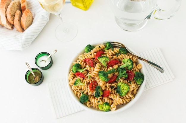 An overhead view of fusilli pasta with vegetables on white background
