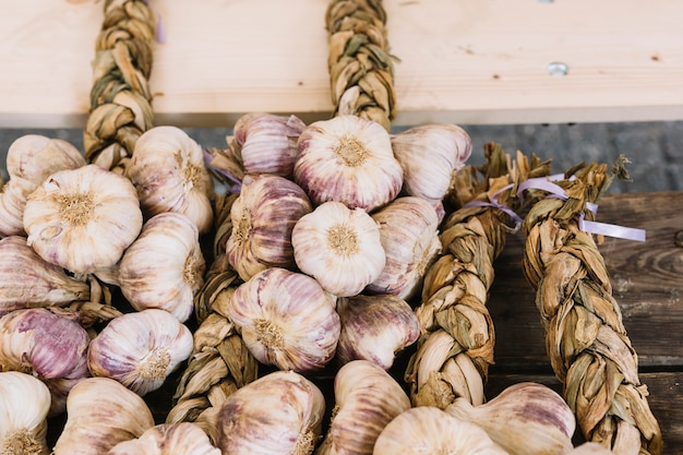 An overhead view of garlic bulb braids on wooden table