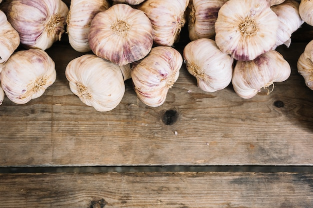 An overhead view of garlic bulbs on wooden table