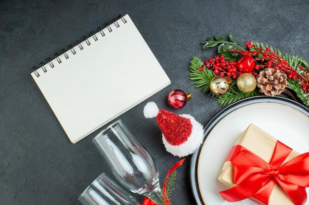 Vista aerea della confezione regalo sulla piastra della cena albero di natale rami di abete cono di conifere cappello di babbo natale calici di vetro caduti notebook su sfondo nero