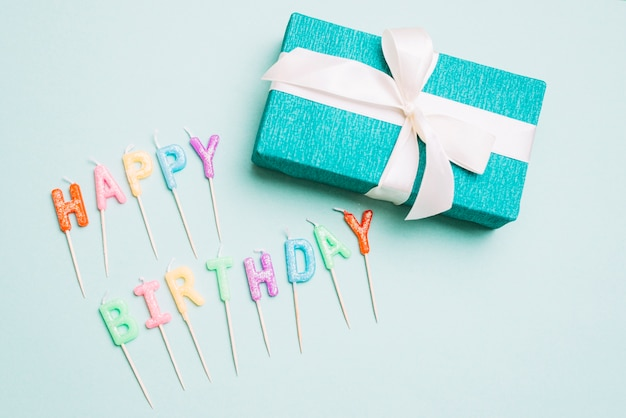An overhead view of gift box and happy birthday candles with stick on blue backdrop