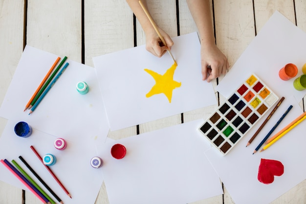 An overhead view of a girl painting the yellow star with paintbrush on white paper