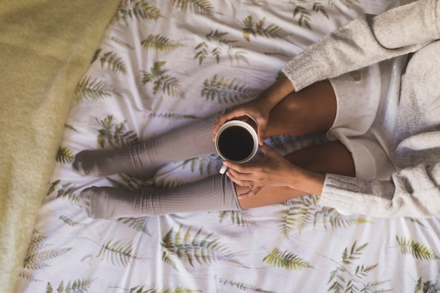 An overhead view of a girl sitting on bed wearing socks holding coffee cup