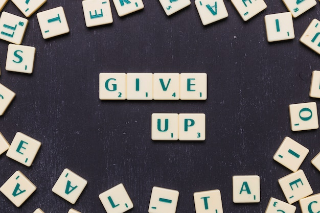 Overhead view of give up text with scrabble letter against black backdrop